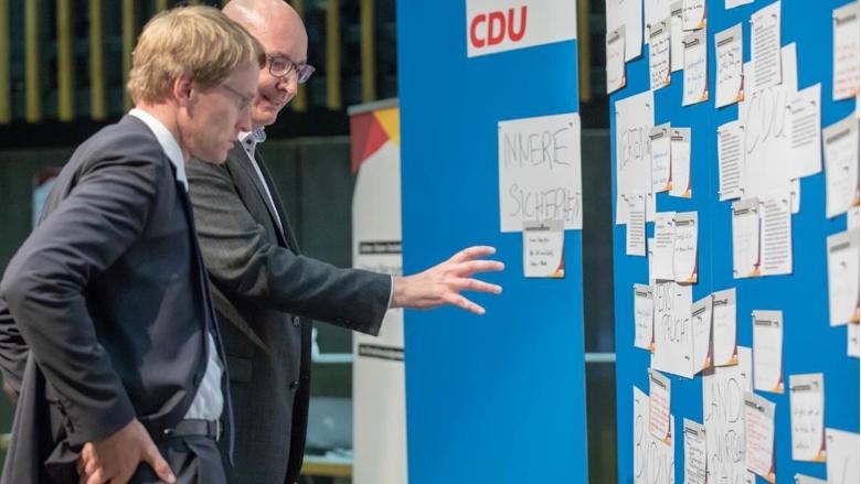 Schleswig-Holsteins Ministerpräsident Daniel Günther wird in die Abläufe der Zuhör-Tour eingeführt