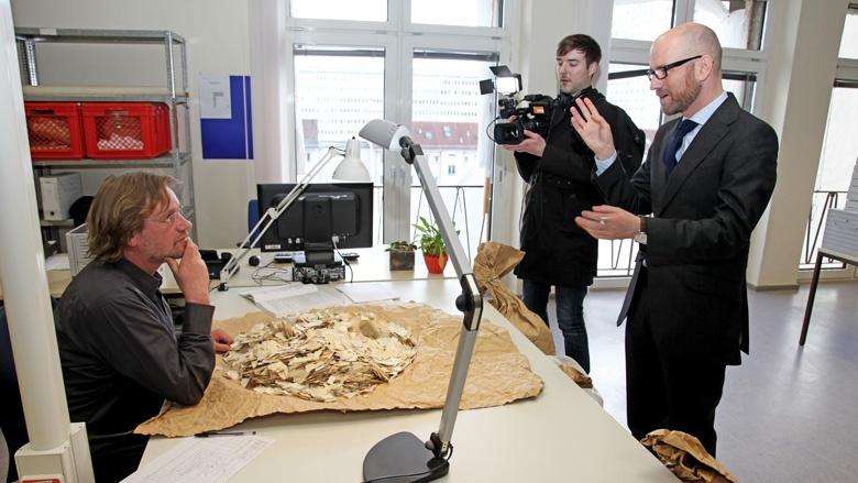 Tauber schaut Mitarbeitern bei der Rekonstruktion von zerrissenen Stasi-Unterlagen zu