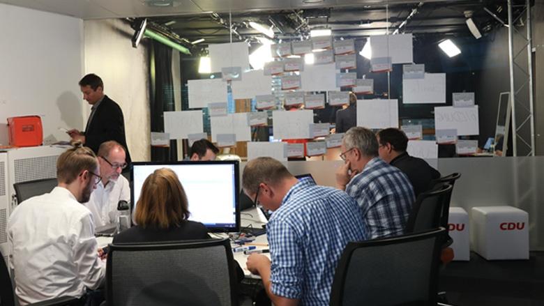 Das Bild zeigt das Team, das im Hintergrund Fragen sammelt und doppelte Fragen selektiert.