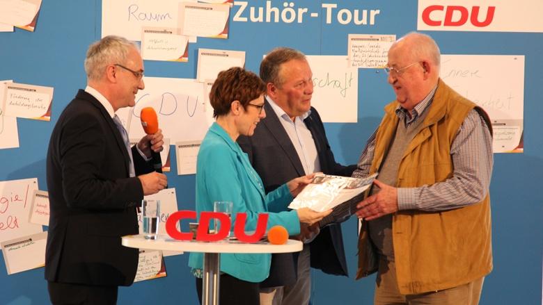 Auf dem Bild sieht man, wie CDU-Generalsekretärin Annegret Kramp-Karrenbauer einem verdienten CDU-Mitglied eine Ehrenurkunde für 50 Jahre Mitgliedschaft in der CDU überreicht.