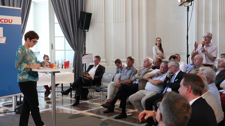 Auf dem Bild richtet ein älteres CDU-Mitglied eine Frage an CDU-Generalsekretärin Annegret Kramp-Karrenbauer.