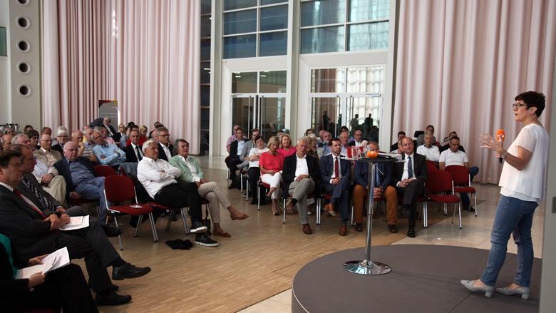 Auf dem Foto sieht man mit Blick von hinten über die Bühne ins Publikum: CDU-Generalsekretärin Annegret Kramp-Karrenbauer hört den CDU-Mitgliedern zu.