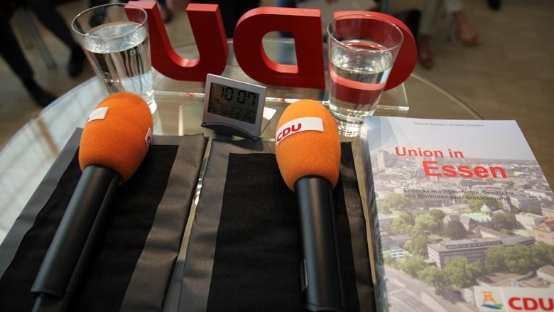 Auf einem Stehtisch seht man zwei CDU-Mikrofone, zwei Gläser Wasser und eine Digitaluhr. Gleich geht es los.