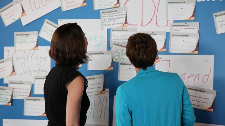 Das Foto zeigt, wie die Generalsekretärin mit der Moderatorin Fragen an der blauen Wand liest.