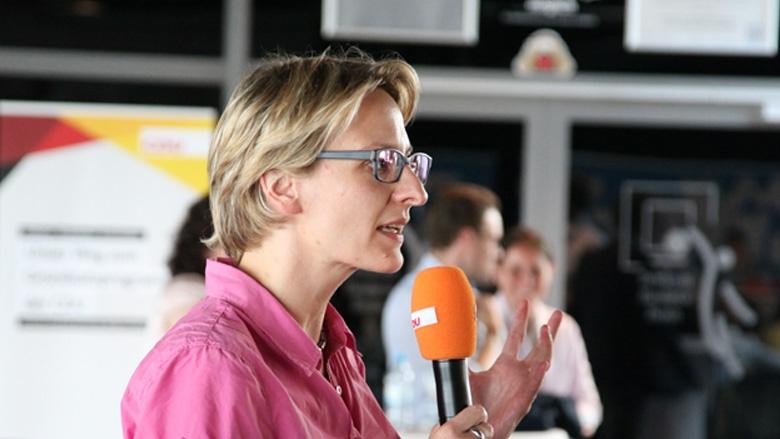 Das Foto zeigt eine junge Frau in Bonn am Mikrofon. Sie stellt Fragen an die CDU-Generalsekretärin.