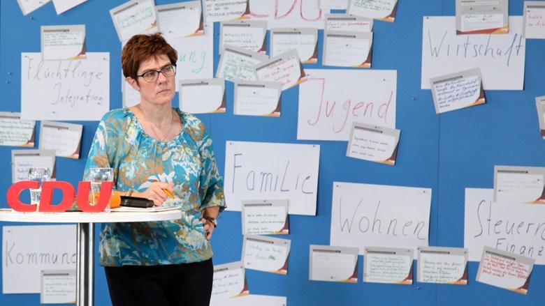 Das Bild zeigt die CDU Generalsekretärin vor einer blauen Rückwand. Sie lauscht Fragen der Mitglieder.