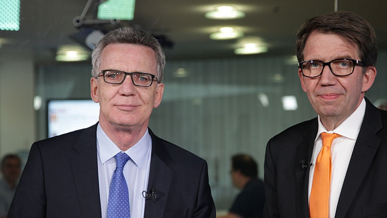 Bundesinnenminister Thomas de Maizière mit dem Moderator der Videokonferenz Frank Bergmann