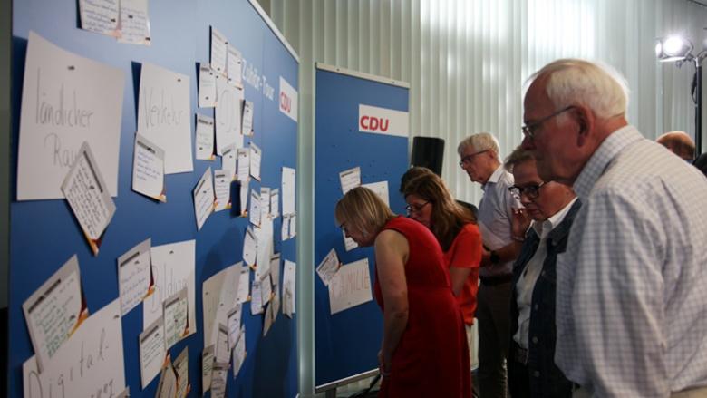 Auf dem Bild sieht man CDU-Mitglieder vor den blauen Pinnwänden, an denen viele Fragen auf Karten hängen.