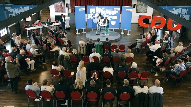 Auf dem Bild sieht man: Der Saal im Kulturbahnhof Greifswald ist voller Menschen.