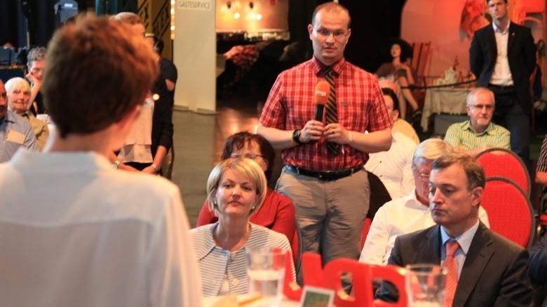 Teilnehmer der Zuhör-Tour in Leipzig stellt Kramp-Karrenbauer eine Frage