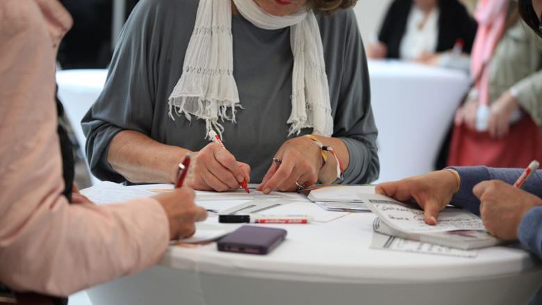 Auf dem Bild sieht man, wie Frauen Fragen auf Karten schreiben.