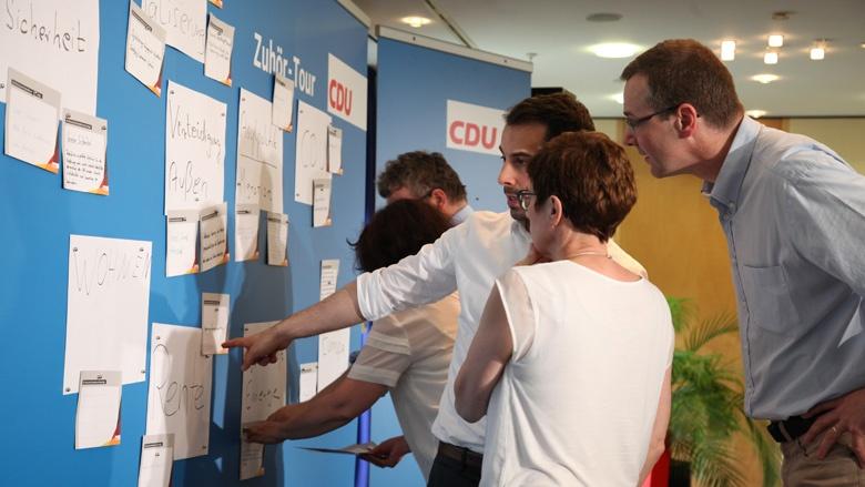 Das Bild zeigt: CDU-Generalsekretärin Annegret Kramp-Karrenbauer liest an einer blauen Wand die Fragen der Mitglieder