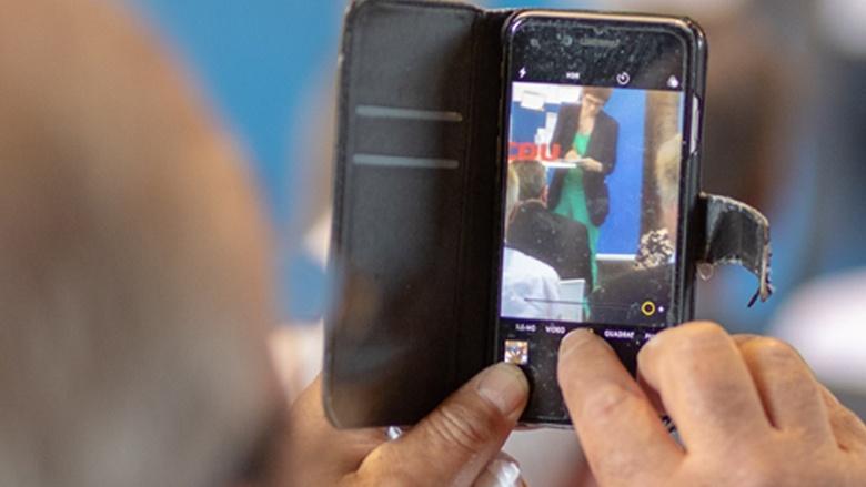 Auf dem Bild sieht man einen älteren hherrn auf einem sehr alten Handy ein Foto der CDU-Generalsekretärin machen.