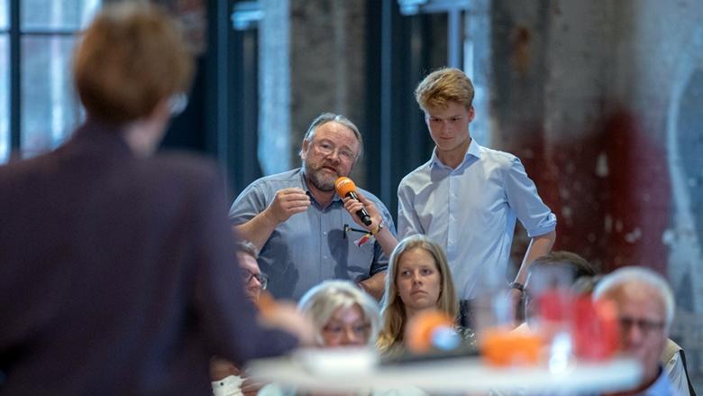 Auf dem Bild sieht man zwei Mitglieder, die in Lübeck Fragen stellen an CDU-Generalsekretärin Annegret Kramp-Karrenbauer.