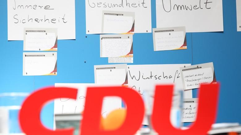 Das Bild zeigt: Fragen der Teilnehmer der Zuhör-Tour in Quedlinburg an einer blauen Wand mit roten CDU-Buchstaben in Vordergrund