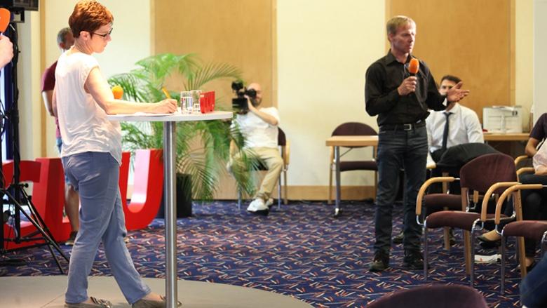 Das Bild zeigt: Ein Teilnemer erläutert der Generalsekretärin seine Fragen.