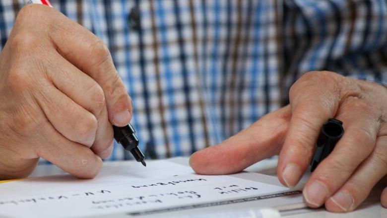 Ein Mann schreibt seinen Beitrag zur Diskussion um das CDU-Grundsatzprogramm auf eine Karteikarte