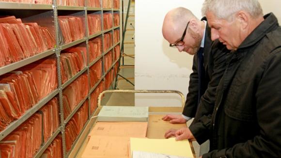 Peter Tauber und Roland Jahn blicken in Akten des ehemaligen MfS.