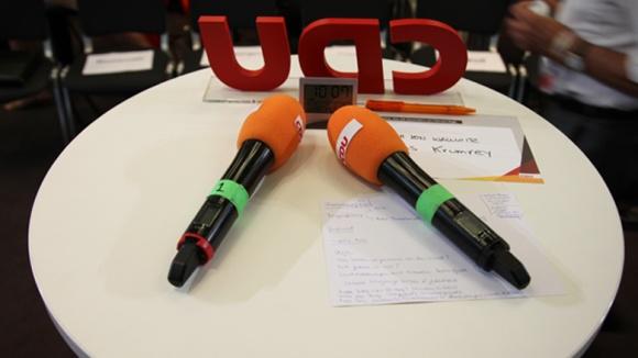 Das Bild zeigt zwei Mikrofone auf einem Tisch. Gleich get es los.