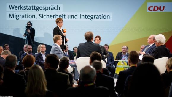 Annegret Kramp-Karrenbauer begrüßte die Podiumsteilnehmer und Gäste vom Rundpodium aus freisprechend mit Handmikrofon.